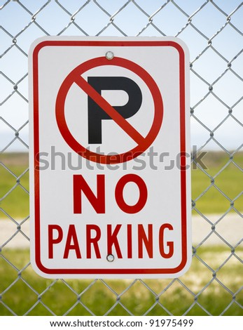 No Parking sign on fence by open countryside