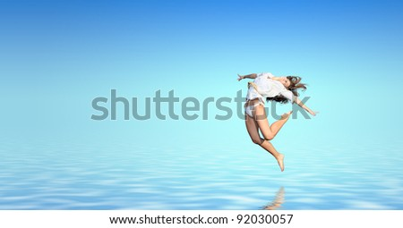 Young woman jumping in the water #92030057
