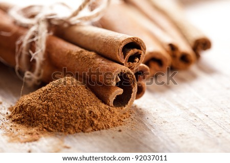Cinnamon sticks and meal close up on wooden table Royalty-Free Stock Photo #92037011