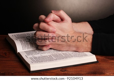 Hands folded in prayer over a Holy bible on wooden table on grey background #92104913
