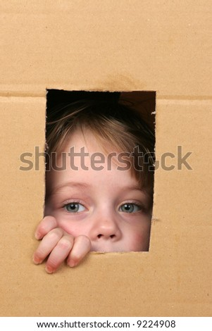 young girl looking from brown carton box #9224908