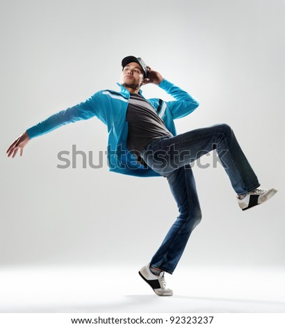 modern hip hop dancer lifts his leg and does some moves while dressed in trendy modern clothing #92323237