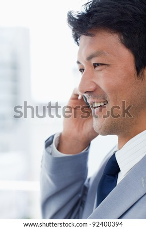 Portrait of a smiling office worker on the phone in his office #92400394