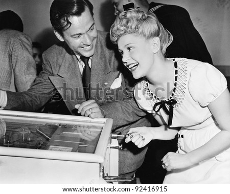 Couple having fun and laughing next to a pinball machine Royalty-Free Stock Photo #92416915