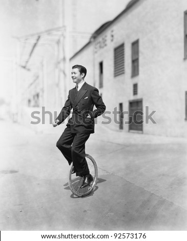Profile of a young man riding a unicycle #92573176