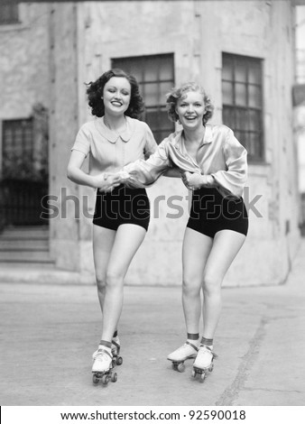 Portrait of two young women with roller blades skating on the road and smiling #92590018