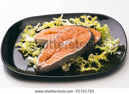 raw salmon slices on a black dish with green salad #92761720