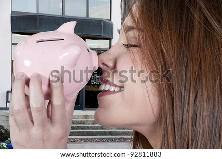 A beautiful woman holding a piggy bank full of money she has saved #92811883