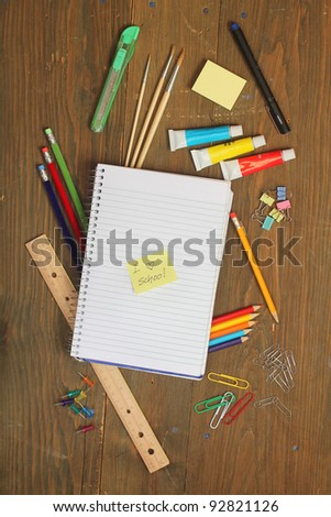 "School material, pencil, rule, brushes, paper clips on a wooden table with a note book with a postite with "" I love school"" write on it #92821126"