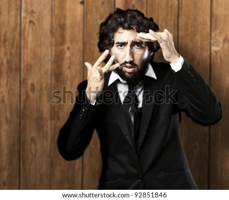 portrait of business man touching his face against a wooden wall