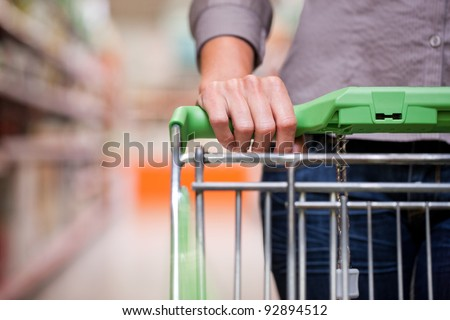 Closeup of female shopper with trolley at supermarket Royalty-Free Stock Photo #92894512