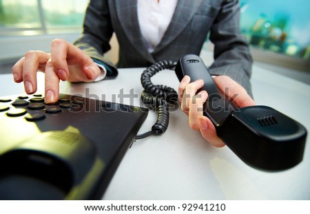 Female hand holding phone receiver and dialing number #92941210