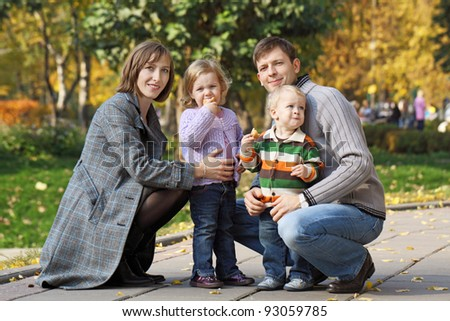 Young family with two children walk in the autumn park #93059785