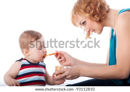 Young mother feeds  her baby on a white background. Happy family. #93112810