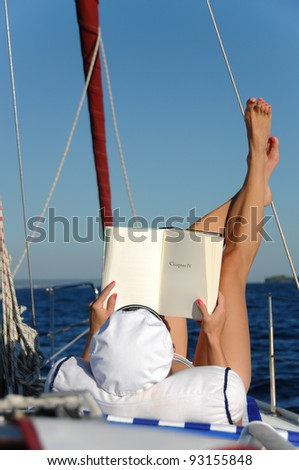 Young beautiful woman is relaxing and sunbathing while reading a book on a sailboat in the open adriatic sea. Book can be used as copy space for small alterations. #93155848