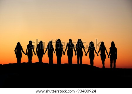 Sunrise silhouette of 10 young women walking hand in hand. Royalty-Free Stock Photo #93400924