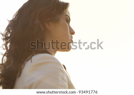 Profile portrait of a woman against the sky with sun rays bathing her face. #93491776