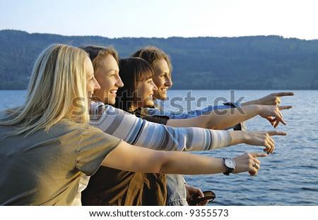 Four girls having fun beside a lake. #9355573