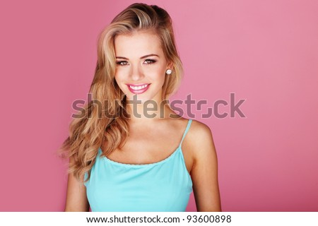Pretty young woman smiling against a pink background