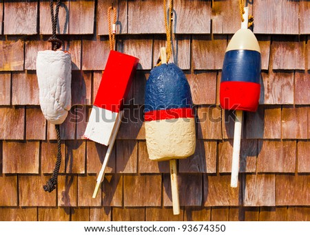 Red white and blue vintage fishing buoys hanging on wood shingled wall