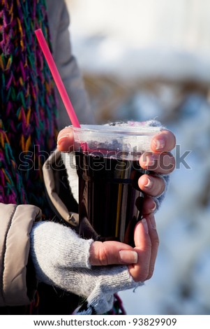 girl holding a glass of hot wine outdoors during winter #93829909