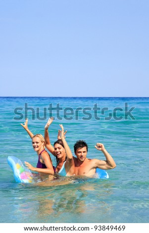 Group of three friends - man and women - on the beach having lots of fun in their vacation in Greece #93849469