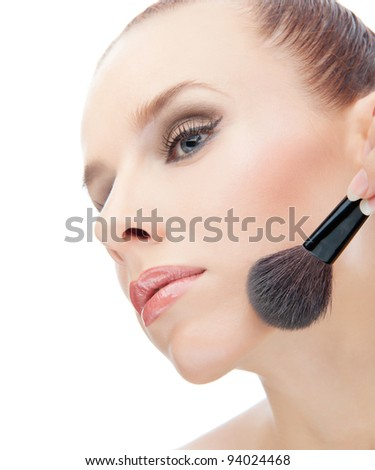Attractive beautiful young women applying blusher and looking out of camera on white background #94024468