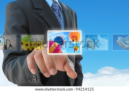 businessman hand pushing a button streaming images on a touch screen interface