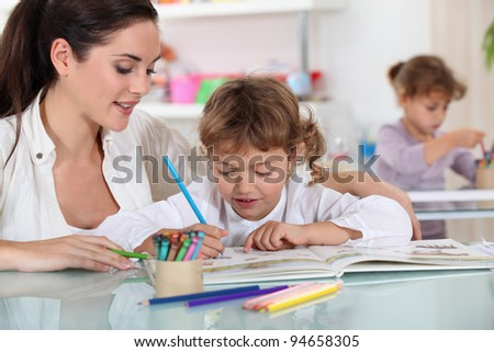 Woman and child colouring at a desk #94658305