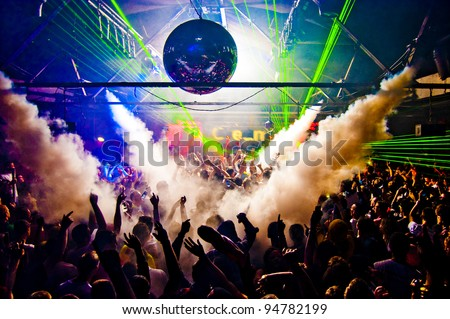 Hands In Air Rave With Smoke Machine and Laser Crowd - Nightclub Royalty-Free Stock Photo #94782199