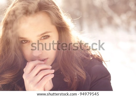 beautiful girl freezing in winter park. pictures in warm colors