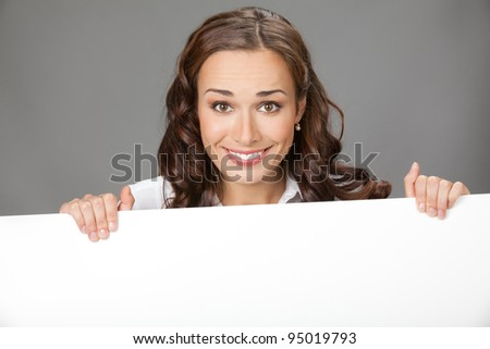 Happy smiling young business woman showing blank signboard, over grey background #95019793