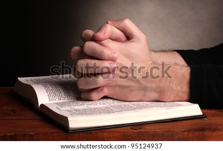Hands folded in prayer over a Holy bible on wooden table on grey background #95124937