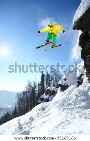 Skier jumping against blue sky from the rock #95169166
