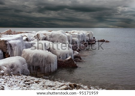 Ice Covered Boulders on Lake Ontario with Stormy Sky #95171959