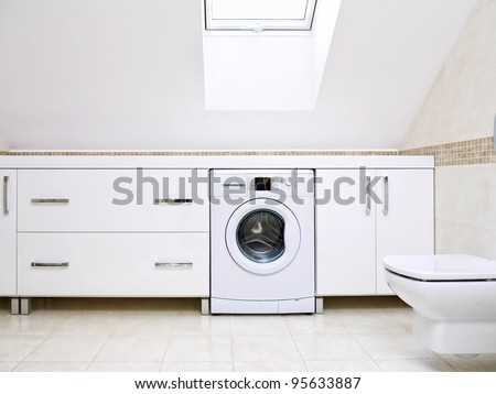 Modern bathroom with shiny white cabinets and washing machine #95633887