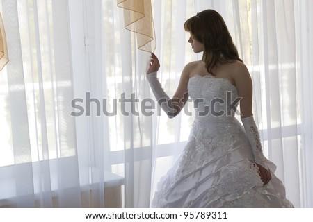 Bride in a beautiful dress by the window #95789311