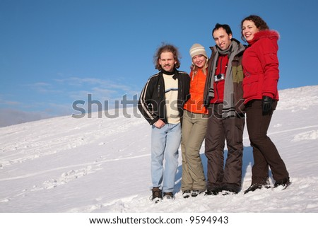 group of friends stand on snow on hillside #9594943