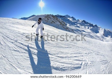 skier skiing downhill on fresh powder snow  with sun and mountains in background #96200669