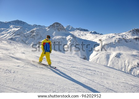 skier skiing downhill on fresh powder snow  with sun and mountains in background #96202952
