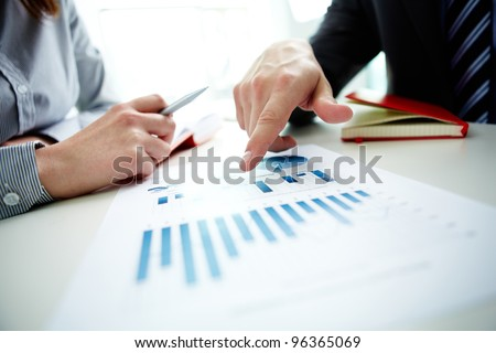 Image of male hand pointing at business document during discussion at meeting Royalty-Free Stock Photo #96365069