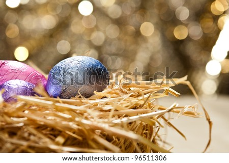 Chocolate Easter eggs in a natural straw nest in front of a beautiful golden background #96511306