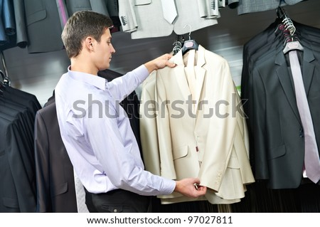 Young man choosing suit jacket during apparel shopping at clothing store #97027811
