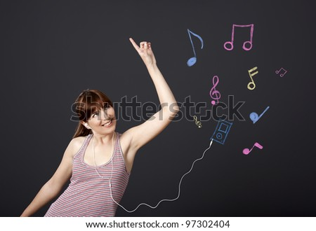Young woman dancing and listen music with musical notes drawn with chalk on a black wall