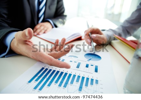 Image of male hand pointing at business document during discussion at meeting Royalty-Free Stock Photo #97474436