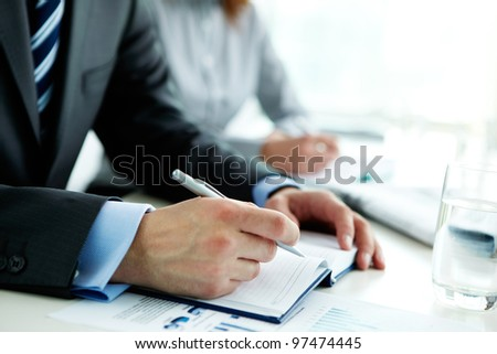 Image of male hand with pen over open notebook at seminar #97474445