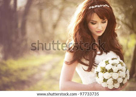 Beautiful bride outdoors in a forest. Royalty-Free Stock Photo #97733735