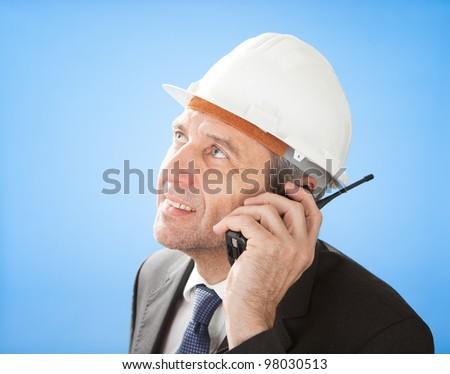 Portrait of senior architect talking on walkie-talkie at construction #98030513