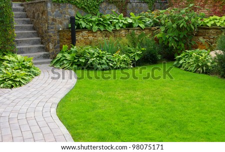 Garden stone path with grass growing up between the stones #98075171