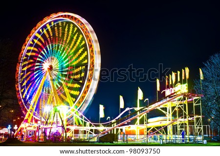 Amusement park at night - ferris wheel and rollercoaster in motion #98093750